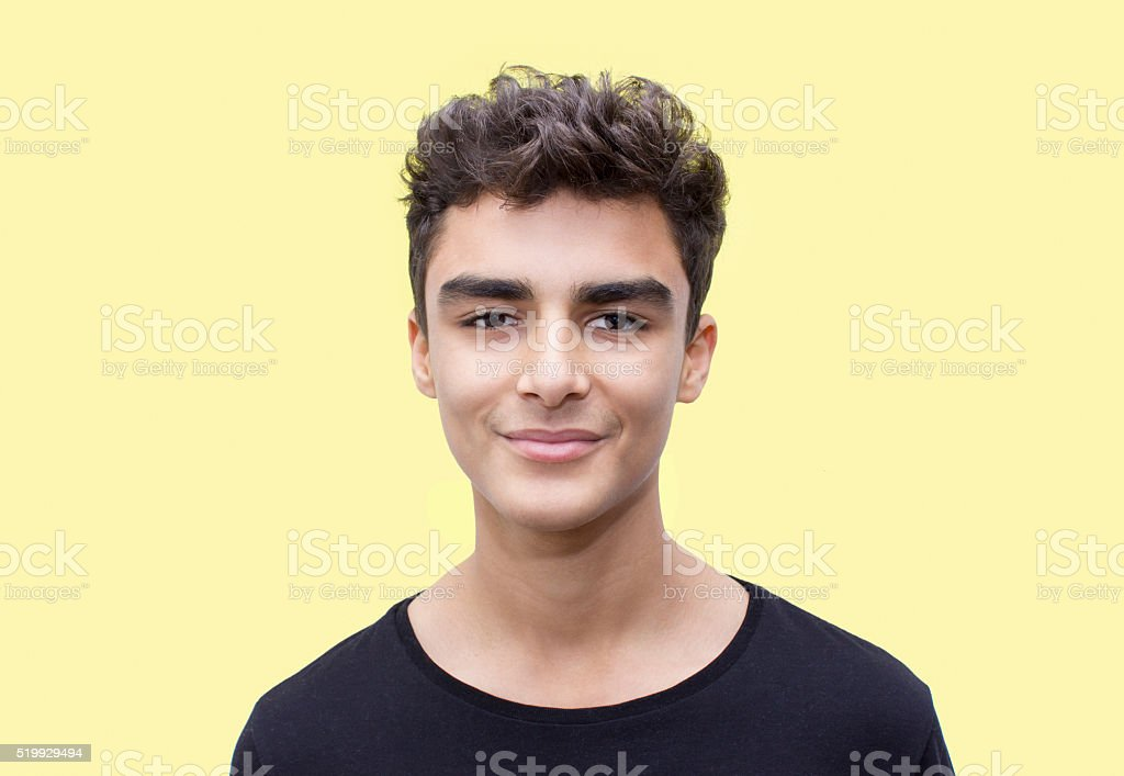 Portrait of smiling boy over yellow background stock photo