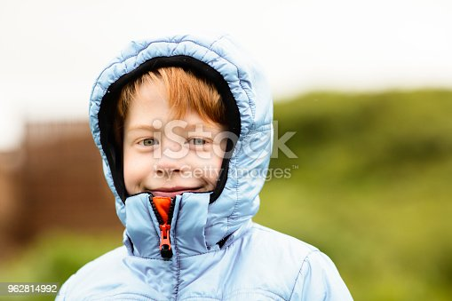 Portrait of boy wearing hooded jacket. Confident male is smiling outdoors. Child is with green eyes.