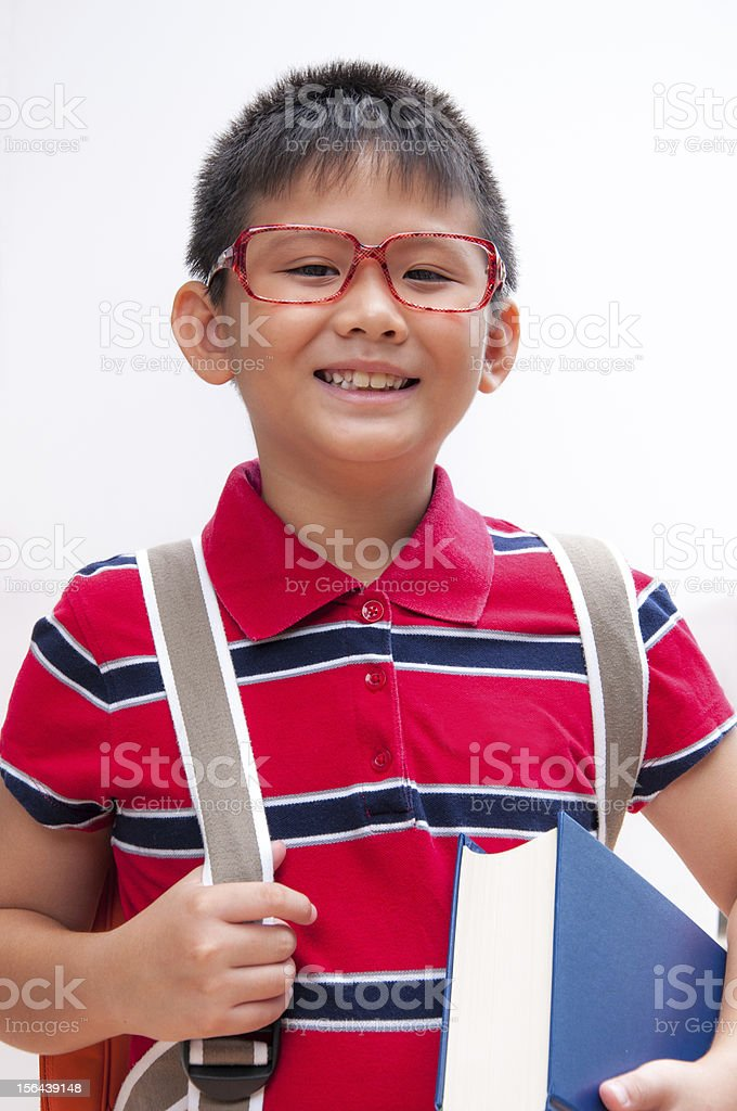 Portrait of smiling boy with bag and book. royalty-free stock photo