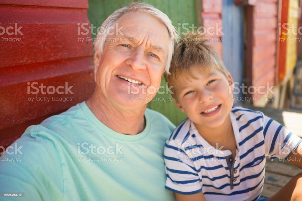 Portrait of smiling boy with grandfather sitting by wall foto de stock royalty-free