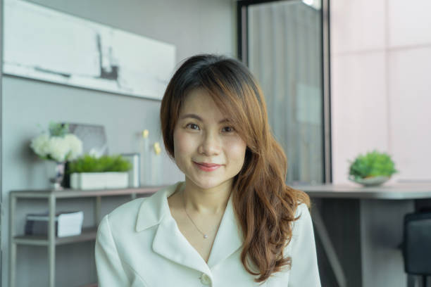 Portrait of smiling business Asian, Chinese woman person working from home and talking to her colleagues in webcam group video call conference on internet online in quarantine in corona virus pandemic stock photo