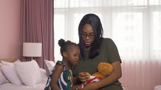 Portrait of smiling business black African american woman, a mom with her daughter playing a bear doll toy in family relationship concept on pink background. A black kid toddler girl with her parent.