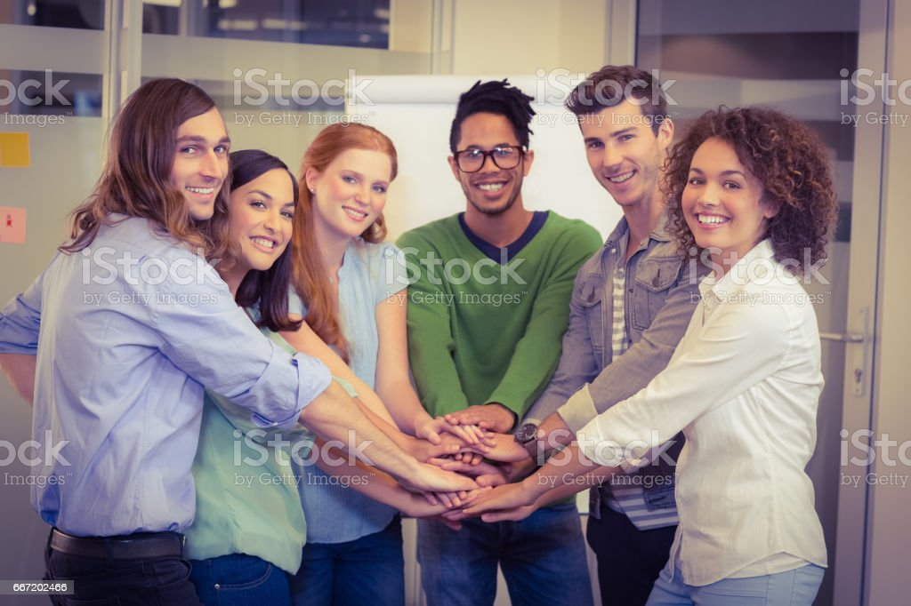 Portrait of smiling business people with hand stacked royalty-free stock photo
