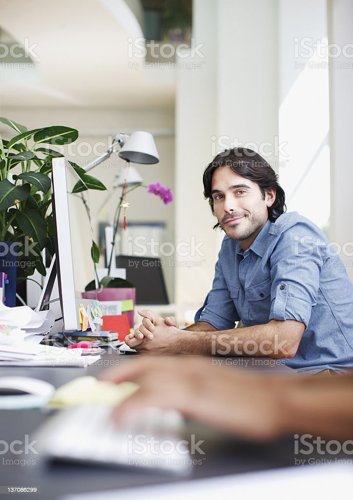 Portrait of smiling businessman at computer in office royalty-free stock photo