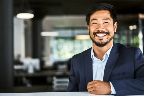 Portrait of smiling businessman at desk in office stock photo