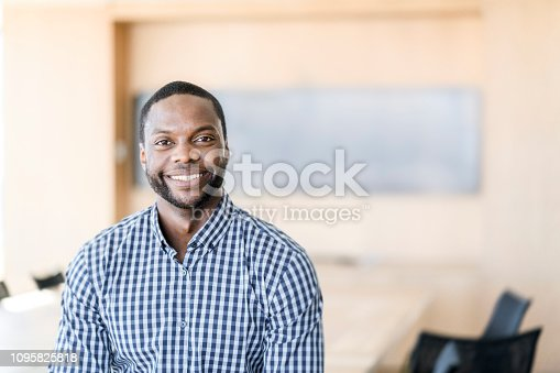 Portrait of smiling businessman. Male professional is wearing casuals. He is at office.