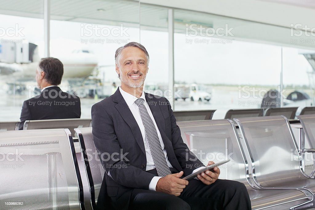 Portrait of smiling businessman holding digital tablet in airport royalty-free stock photo