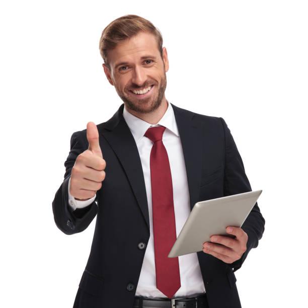 微笑商人的肖像持有平板電腦和做 ok 標誌 - thumbs up 個照片及圖片檔