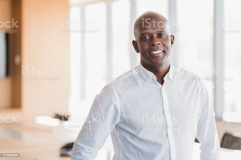 Portrait of smiling businessman in board room stock photo