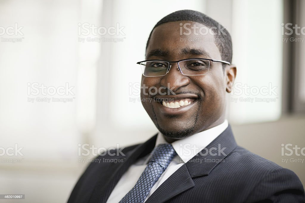 Portrait of smiling businessman in glasses, head and shoulders stock photo