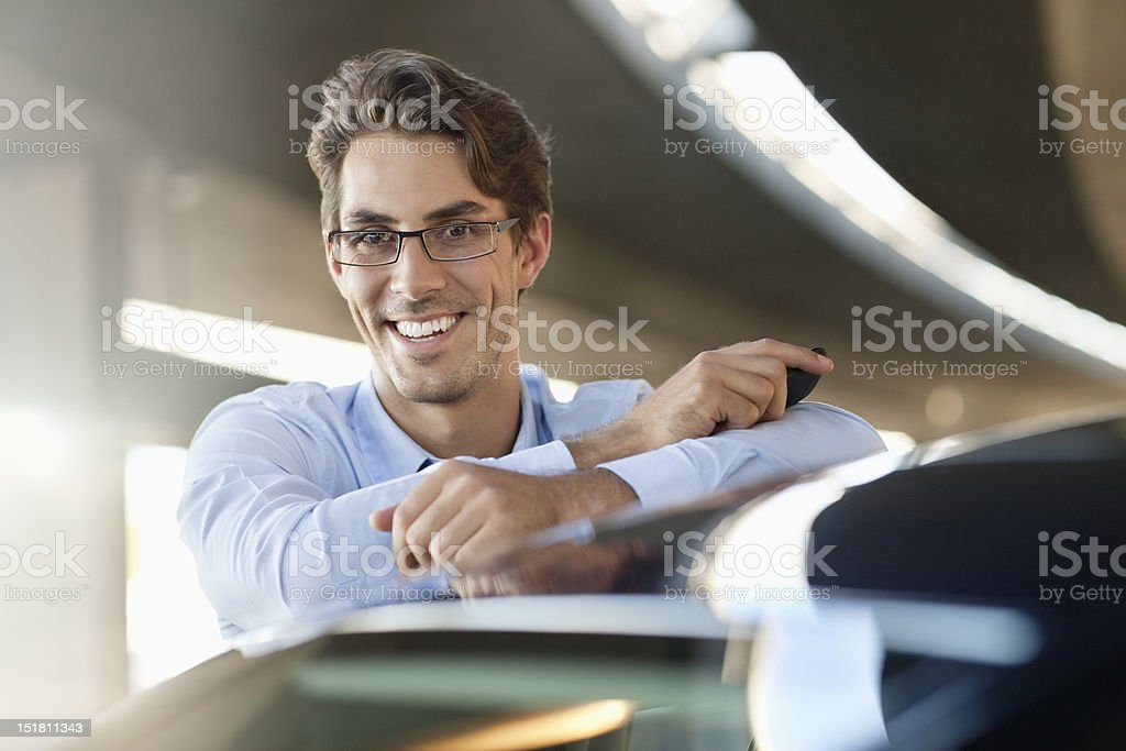 Portrait of smiling businessman leaning on car stock photo