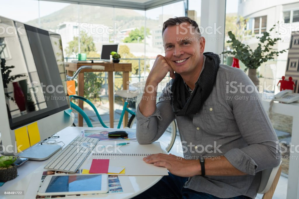 Portrait of smiling businessman sitting at desk stock photo