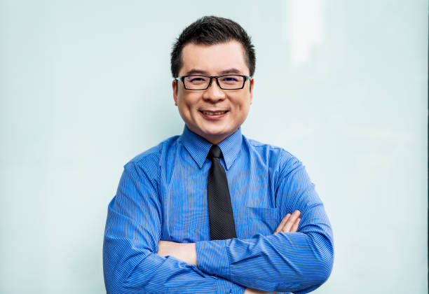 Portrait of smiling businessman with arms crossed stock photo