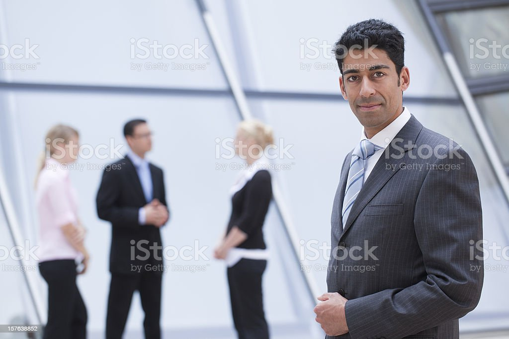 Portrait of smiling businessman with group in background royalty-free stock photo