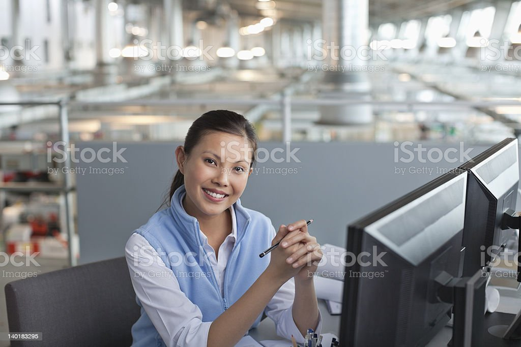 Portrait of smiling businesswoman at computer in factory royalty-free stock photo