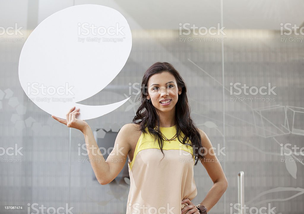 Portrait of smiling businesswoman holding speech bubble stock photo