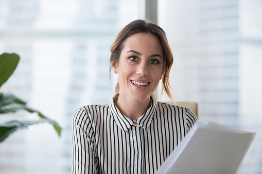 Portrait of smiling millennial businesswoman holding documents looking at camera, headshot of happy woman worker or female ceo posing with paperwork making picture at corporate photoshoot.