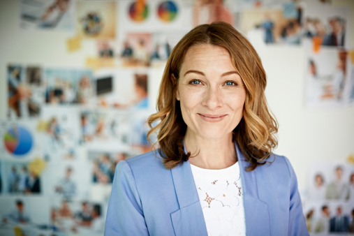 Portrait of confident businesswoman in front of wall with pictures
