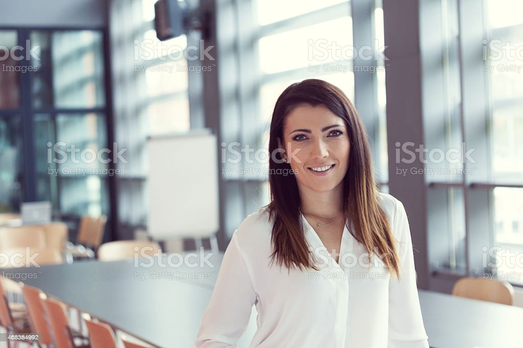 Portrait of smiling businesswoman standing in an office Portrait of beautiful businesswoman wearing white shirt, standing in a board room in an office and smiling at camera.  2015 Stock Photo