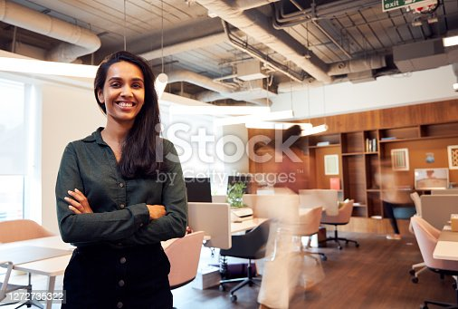 Portrait Of Smiling Businesswoman Standing In Busy Modern Open Plan Office