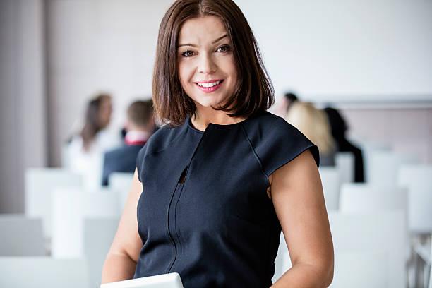 portrait of smiling businesswoman standing in seminar hall - 30 39 jaar stockfoto's en -beelden