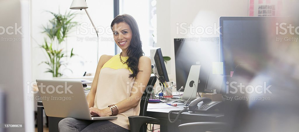 Portrait of smiling businesswoman using laptop in office royalty-free stock photo