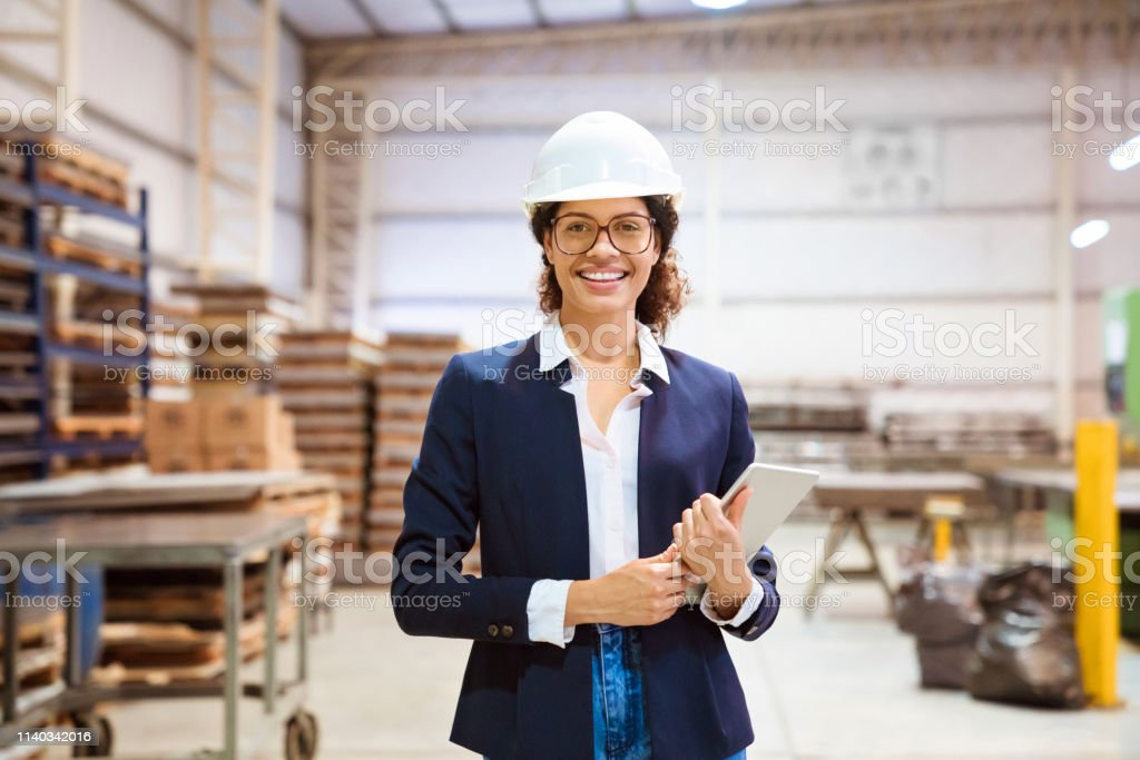 Portrait of smiling businesswoman wearing hardhat Portrait of smiling businesswoman wearing hardhat in industry. Confident inspector is on visit in warehouse. She is holding digital tablet. 30-34 Years Stock Photo