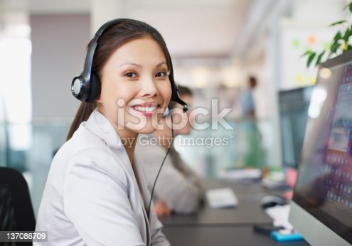 istock Portrait of smiling businesswoman with headset at computer in office 137086709