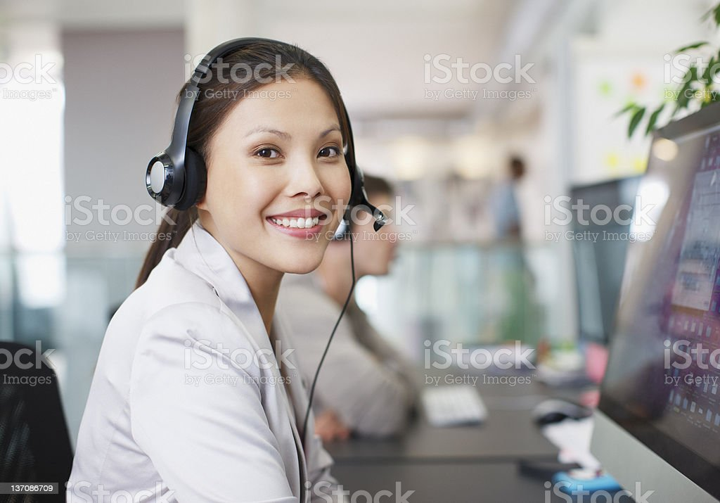 Portrait of smiling businesswoman with headset at computer in office stock photo