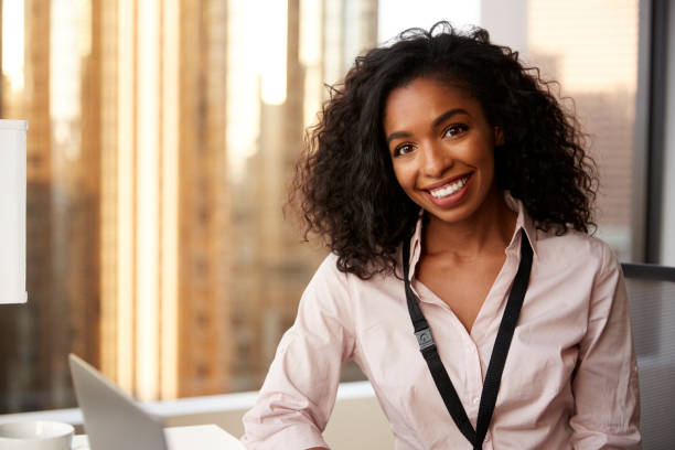 Portrait Of Smiling Businesswoman With Security Pass On Lanyard In Office Portrait Of Smiling Businesswoman With Security Pass On Lanyard In Office monkeybusinessimages stock pictures, royalty-free photos & images