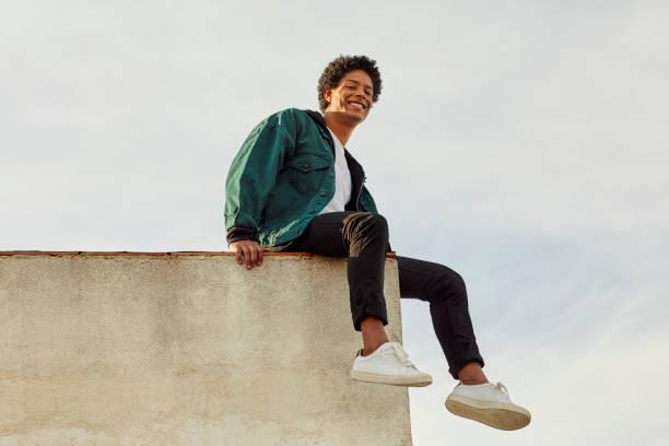 portret van glimlachen zorgeloze man op dak - laag camerastandpunt stockfoto's en -beelden