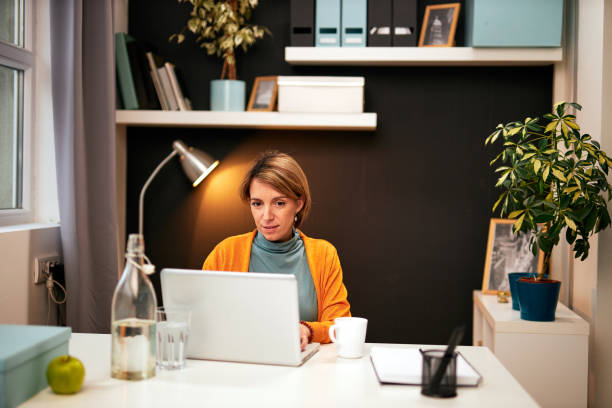 Portrait of smiling Caucasian businesswoman sitting in home office working. Work from home concept. stock photo