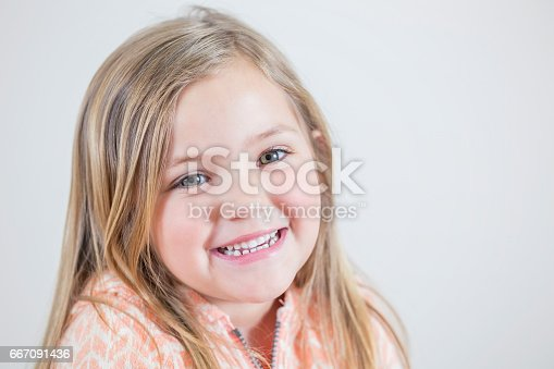 Beautiful Caucasian little girl smiles cheerfully at the camera. She is wearing a sweater.