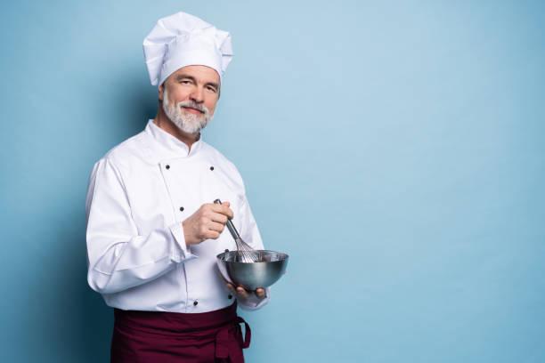 Porträt des lächelnden Kochs hält Schüssel und Draht besen auf blauem Hintergrund. Chef machen Mahlzeit. – Foto