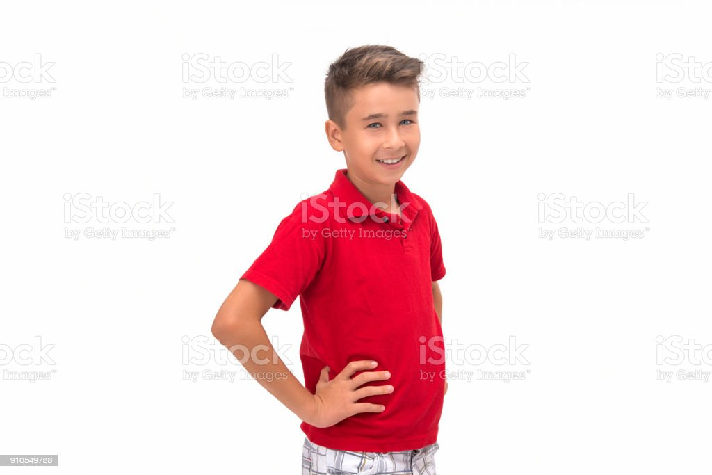 Portrait of smiling child looking at camera in hands on hip position against white background stock photo