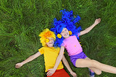 Portrait of smiling children with blue and yellow hair lying on the green grass and waving their hands in pleasure with yellow petals from flowers in summer.