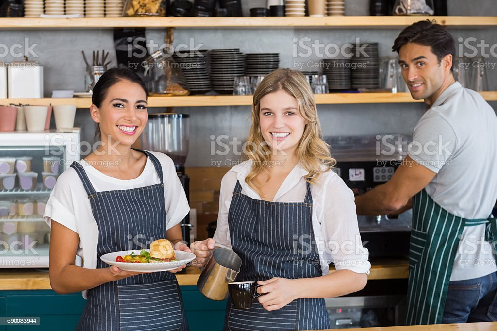 Portrait of smiling colleague working at counter stock photo