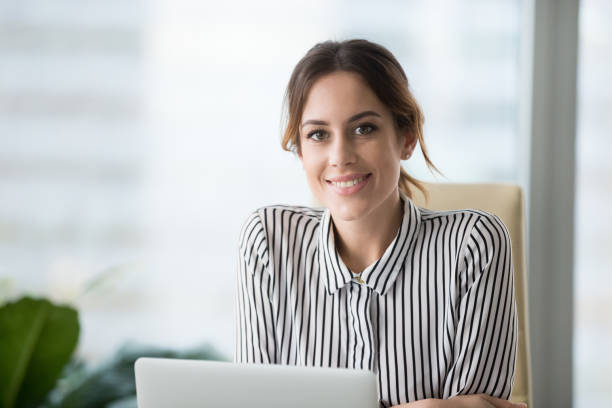 Portrait of smiling confident female boss looking at camera Portrait of smiling beautiful millennial businesswoman or CEO looking at camera, happy female boss posing making headshot picture for company photoshoot, confident successful woman at work leisure equipment stock pictures, royalty-free photos & images