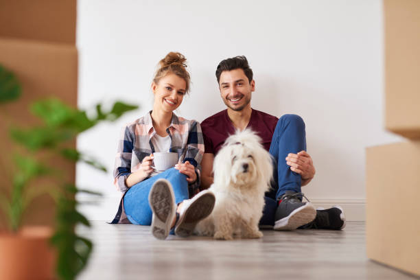 Portrait of smiling couple and dog in their new home stock photo