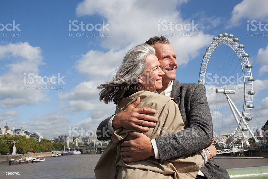 Portrait of smiling couple hugging in front of Thames river royalty-free stock photo