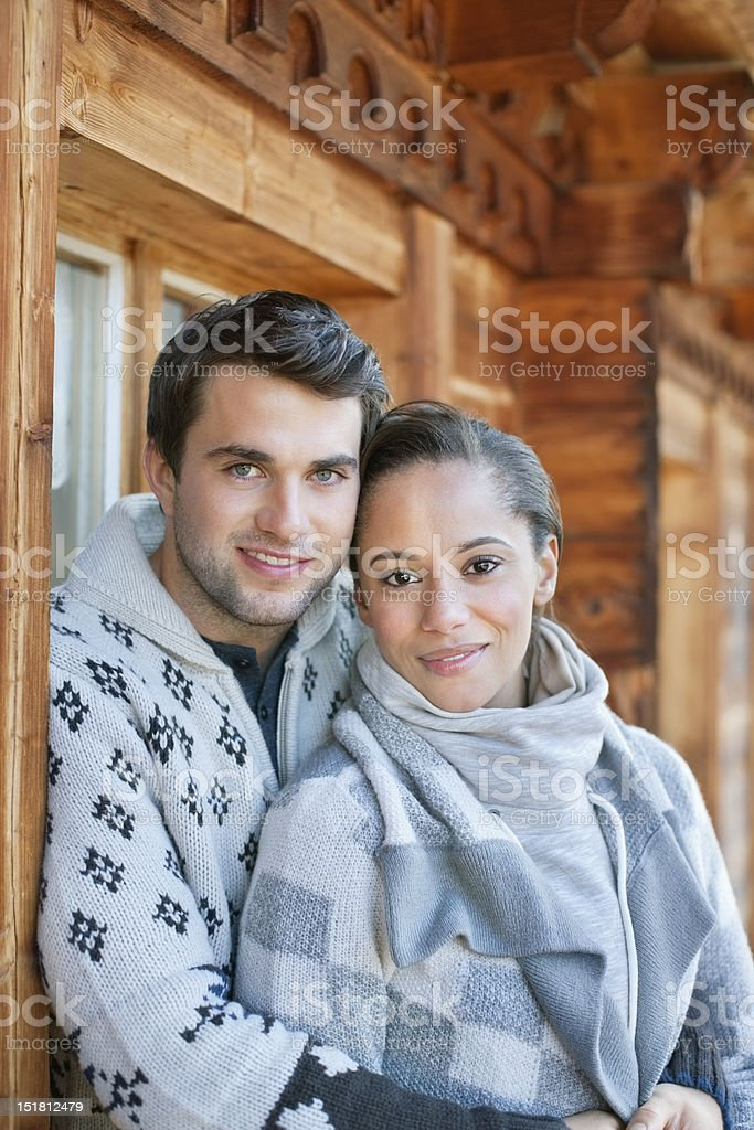 Portrait of smiling couple hugging on cabin porch stock photo