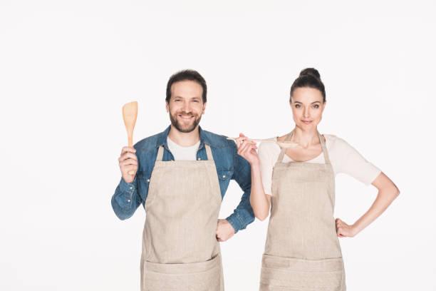 porträt des lächelns paar in schürzen mit hölzernen küchenutensilien isoliert auf weiss - grillschürze stock-fotos und bilder