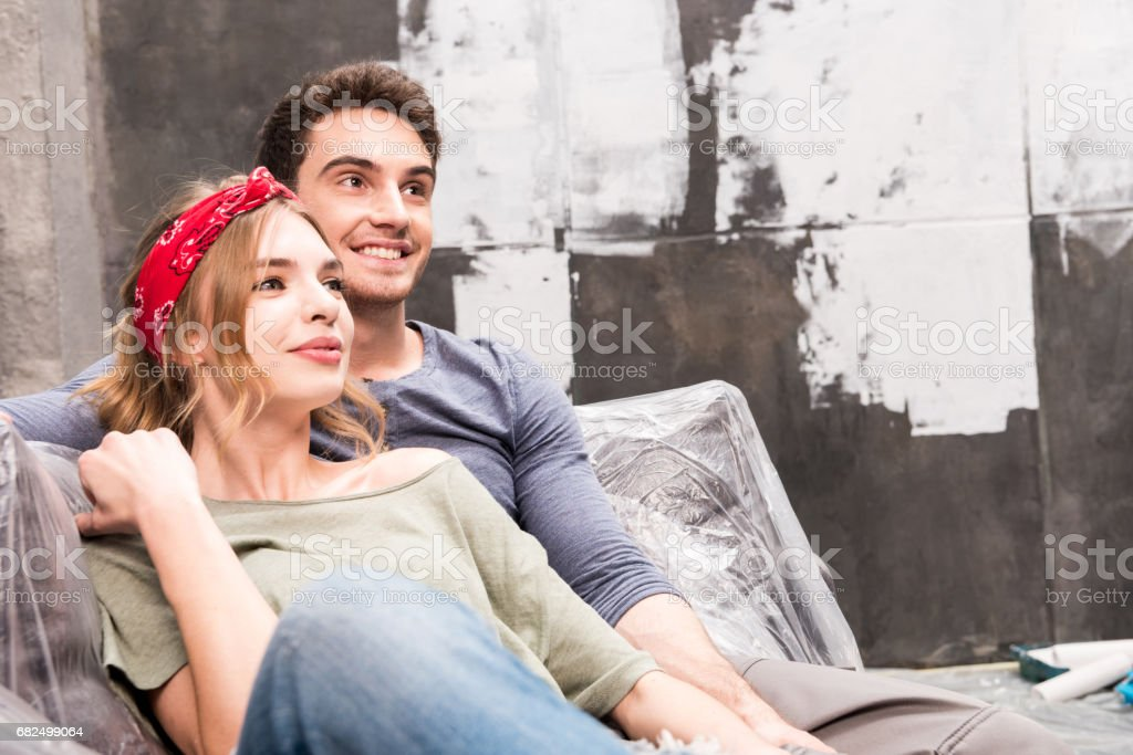 portrait of smiling couple resting on sofa while renovation home photo libre de droits