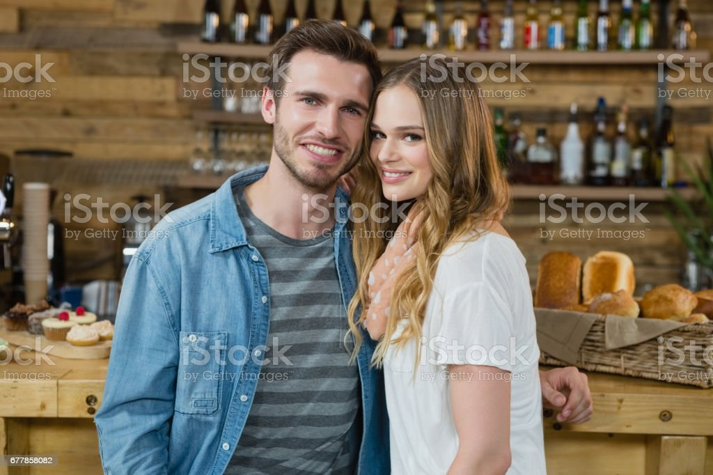 Portrait of smiling couple standing behind the counter royalty-free stock photo