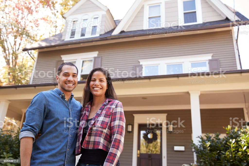 Portrait Of Smiling Couple Standing In Front Of Their Home stock photo