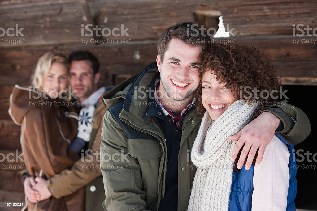 Portrait of smiling couples hugging outside cabin royalty-free stock photo