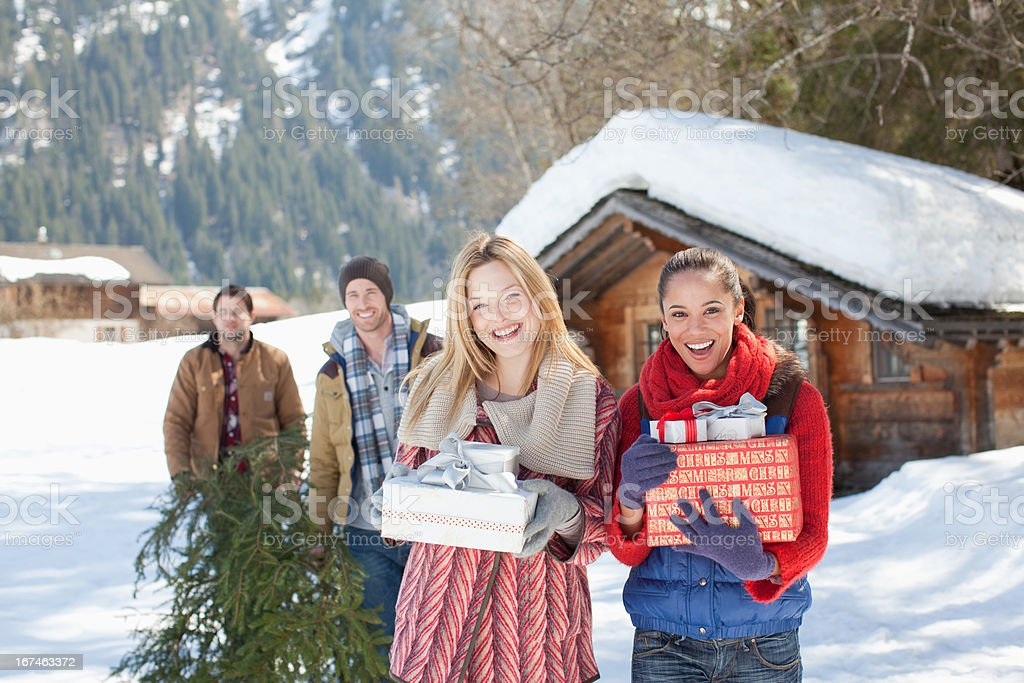 Portrait of smiling couples with fresh cut Christmas tree and gifts in snow royalty-free stock photo