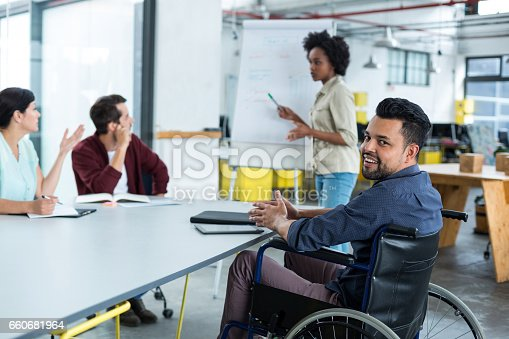istock Portrait of smiling disabled business executive in wheelchair at meeting 660681964