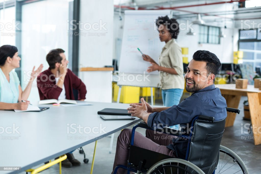 Portrait of smiling disabled business executive in wheelchair at meeting stock photo
