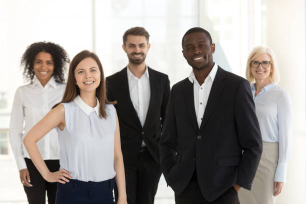 portrait of smiling diverse work team standing posing in office - professional occupation stock pictures, royalty-free photos & images